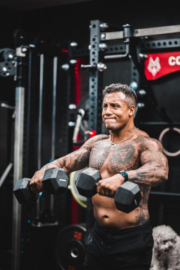 man lifting dumbbells
