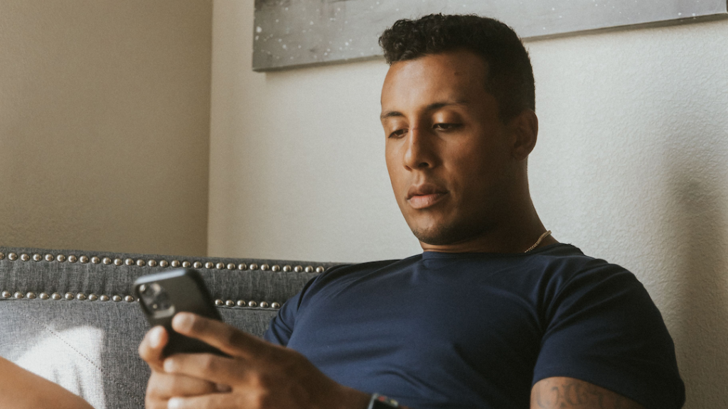 Man sitting in chair working on iphone